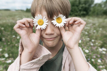 Close-up of boy hiding eyes with chamomile flowers - EYAF01224