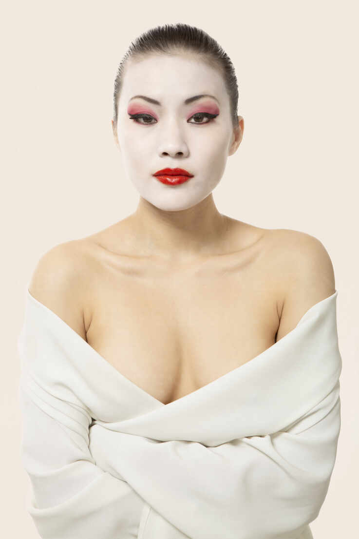 Young woman with opera make-up wrapped in blanket against white background - EAF00025 - Eyes on Asia/Westend61