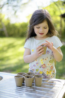 Cute girl planting seeds in small pots on table at garden - BRF01467