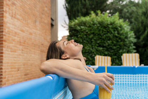 Relaxed woman holding orange juice in inflatable swimming pool at yard - AFVF06819