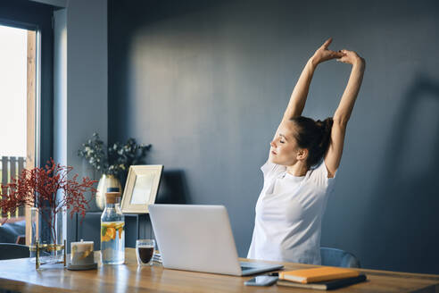 Tired young woman stretching arms while sitting at desk in home office - BSZF01575