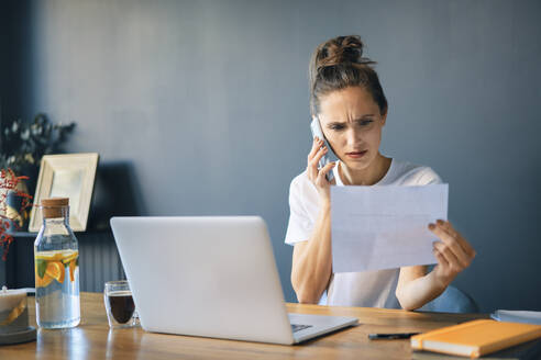 Businesswoman holding document talking over smart phone while sitting at desk in home office - BSZF01578