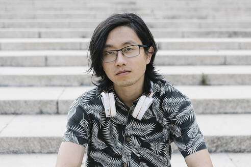 Close-up of young man wearing eyeglasses with headphones sitting on steps in city - XLGF00391