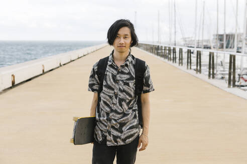 Young man holding skateboard while standing on promenade in city - XLGF00397