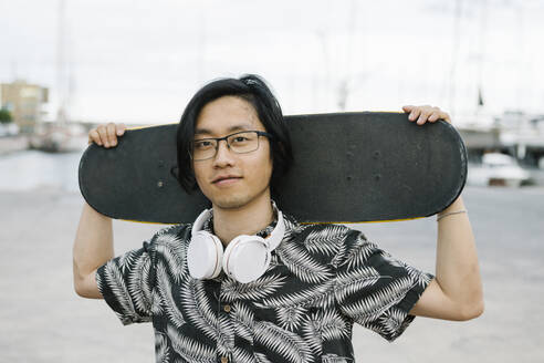 Close-up of young man with headphones holding skateboard while standing in city - XLGF00400
