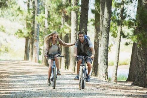 Smiling couple mountain biking in woods - CAIF28562
