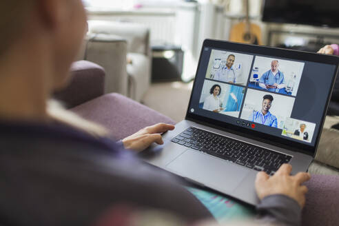 Woman with laptop video chatting with doctors from sofa - CAIF28901