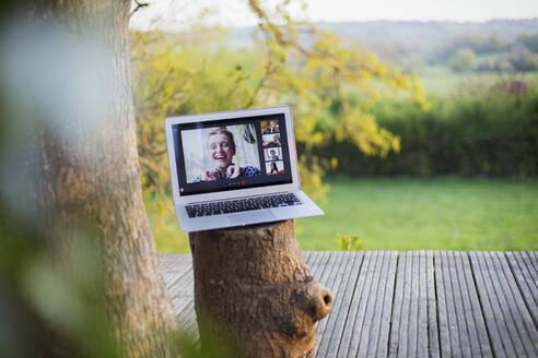 Friends video chatting on laptop screen on idyllic balcony - CAIF28937