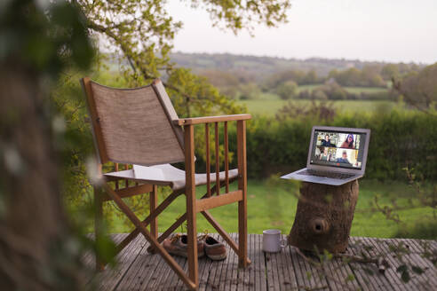 Colleagues video chatting on laptop screen on rural balcony - CAIF28976