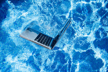 High angle view of laptop floating on swimming pool - JCMF01065