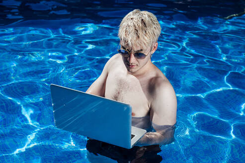 Shirtless young man wearing sunglasses using laptop while standing in swimming pool - JCMF01068