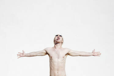 Shirtless young man with arms outstretched and mouth open standing against white wall - JCMF01083