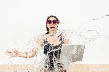 Woman with laptop screaming while water splashing on her against wall - JCMF01086