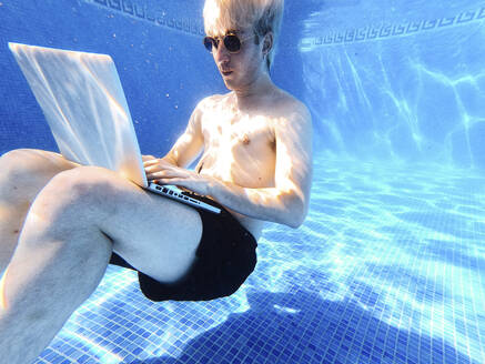 Shirtless young man wearing sunglasses using laptop while swimming underwater in pool - JCMF01092