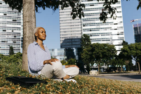 Smiling businesswoman sitting against tree trunk in city - JRFF04635