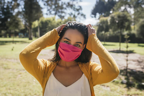 Close-up of young woman wearing mask standing in park during sunny day - DSIF00062