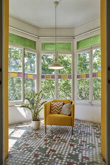 Empty chair by potted plant against window in living room - VEGF02562