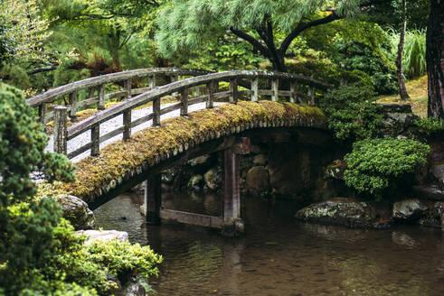 Japan, Kyoto,Footbridge over pond in Japanese garden - EHF00636