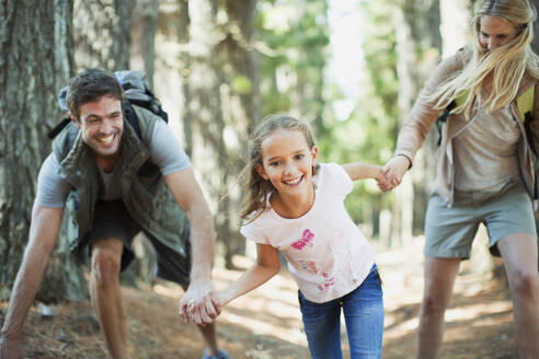 Family holding hands and running in woods - CAIF29134