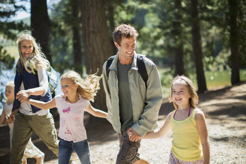 Smiling family holding hands and walking in woods - CAIF29137