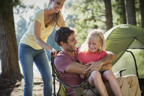 Smiling family at campsite in woods - CAIF29146