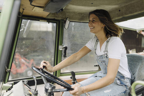 Happy young woman driving tractor - GUSF04211