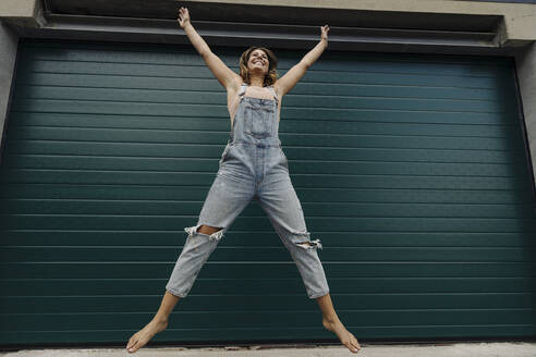 Carefree young woman jumping in front of garage door - GUSF04238