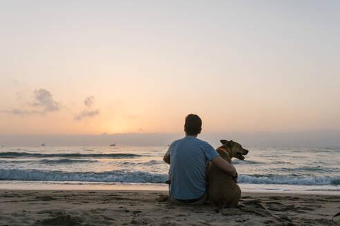 Man sitting with his dog enjoying dawn at beach - EGAF00585