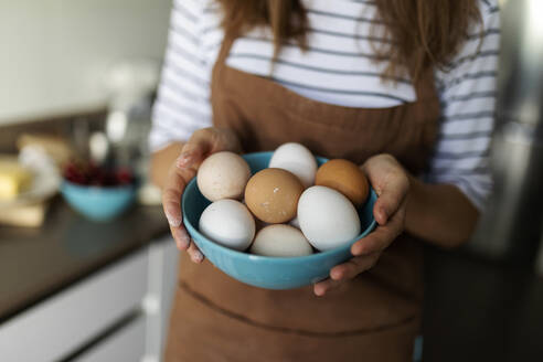 Close-up of young woman holding eggs in kitchen at home - VABF03242