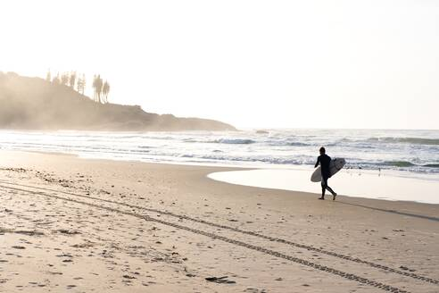 Unrecognizable man running with surf board at the beach - CAVF87459
