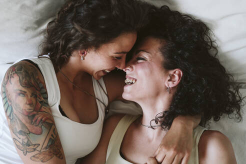 Close-up of happy lesbian couple kissing while lying on bed at home - EBBF00458
