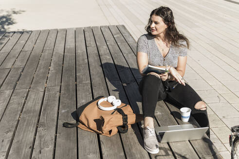 Thoughtful young woman looking away while sitting with laptop and backpack on boardwalk in city - UUF20750