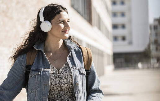 Young woman listening music through headphones looking away while standing in city - UUF20780