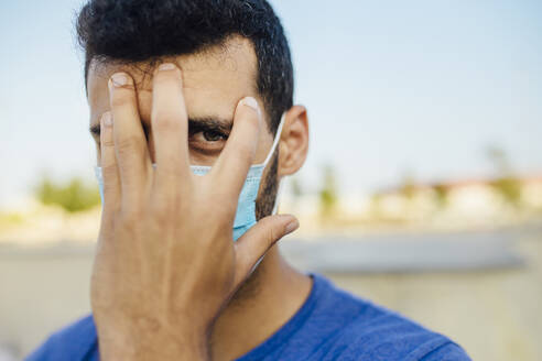 Close-up of young man with hand on face against clear sky - MIMFF00109