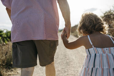 Close-up of grandfather holding granddaughter's hand while walking on dirt road - JRFF04652