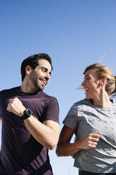 Smiling couple looking at each other while running against clear blue sky - JCMF01097