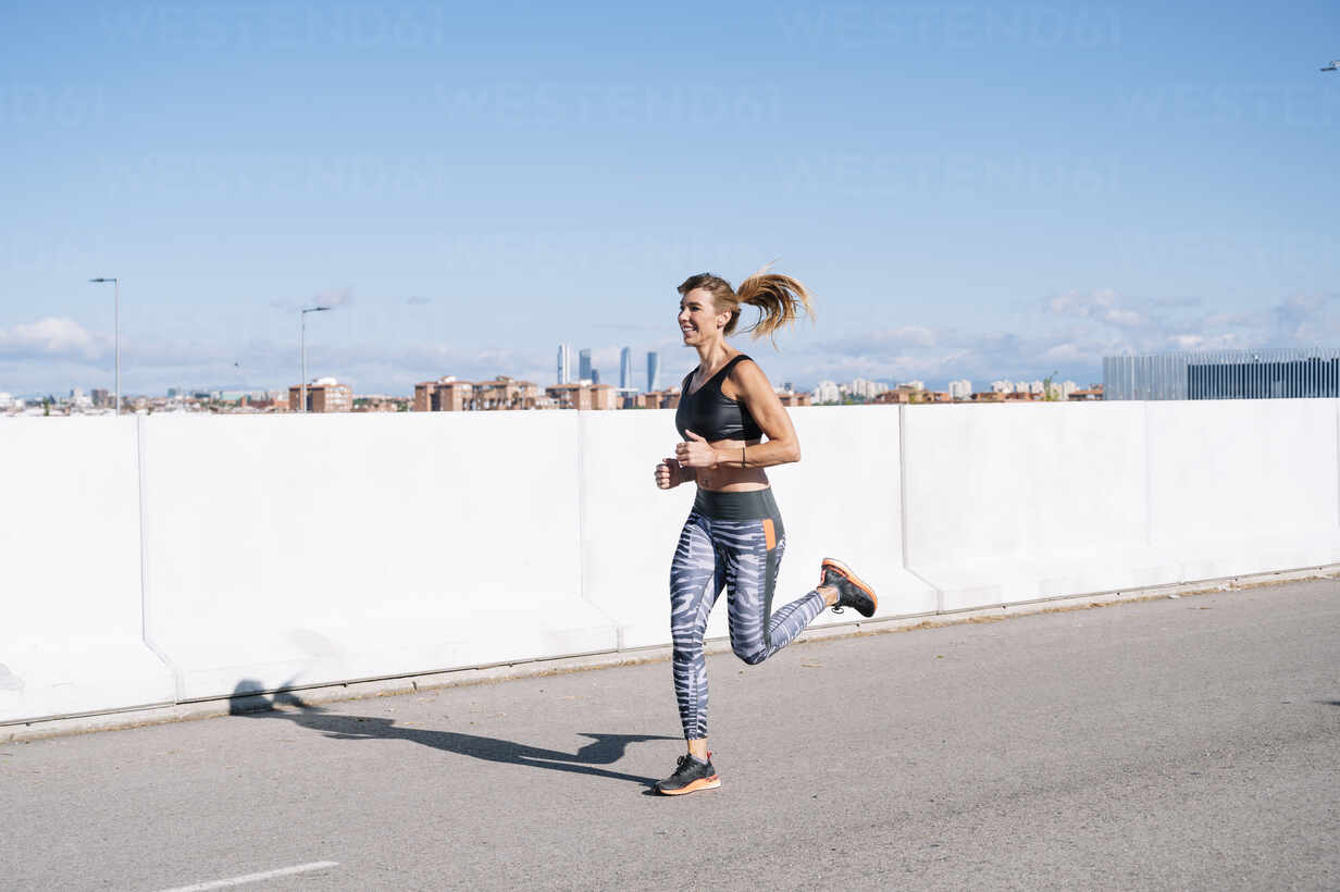 Woman running on road against blue sky in city during sunny day - JCMF01100 - Jose Luis CARRASCOSA/Westend61