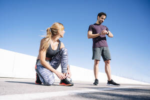 man checking time while woman tying shoelace on road against clear blue sky in city - JCMF01106