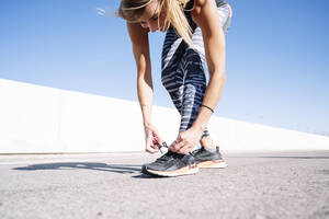 Mid adult woman tying shoelace on road against clear blue sky in city - JCMF01109