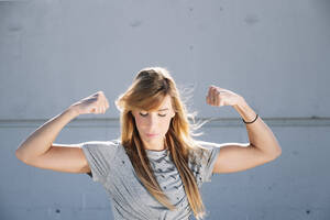 Confident woman flexing muscles while standing against wall in city - JCMF01112