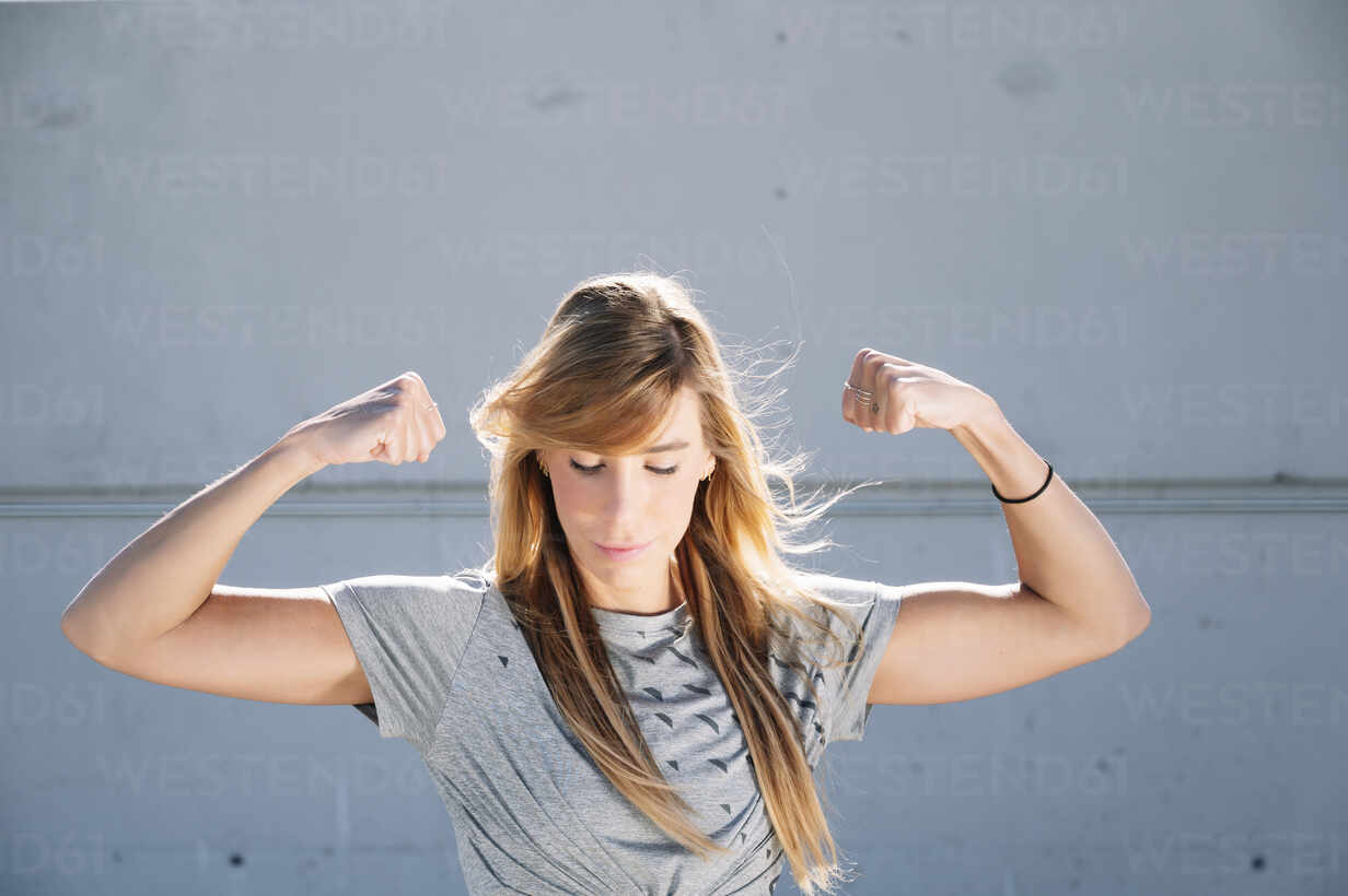 Confident woman flexing muscles while standing against wall in city - JCMF01112 - Jose Luis CARRASCOSA/Westend61