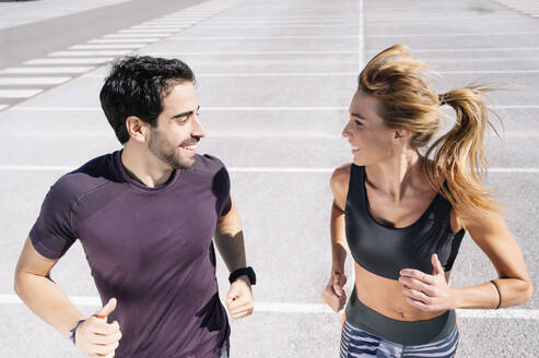 Smiling couple looking at each other while jogging on road in city - JCMF01118