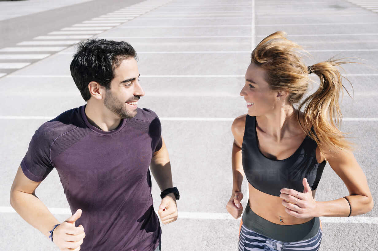 Smiling couple looking at each other while jogging on road in city - JCMF01118 - Jose Luis CARRASCOSA/Westend61