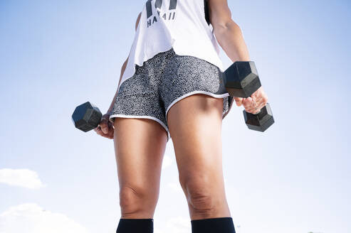 Mid adult woman holding dumbbells standing against sky on sunny day - JCMF01121