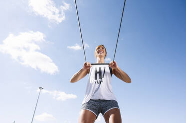 Smiling mid adult woman exercising with strap against sky during sunny day - JCMF01133