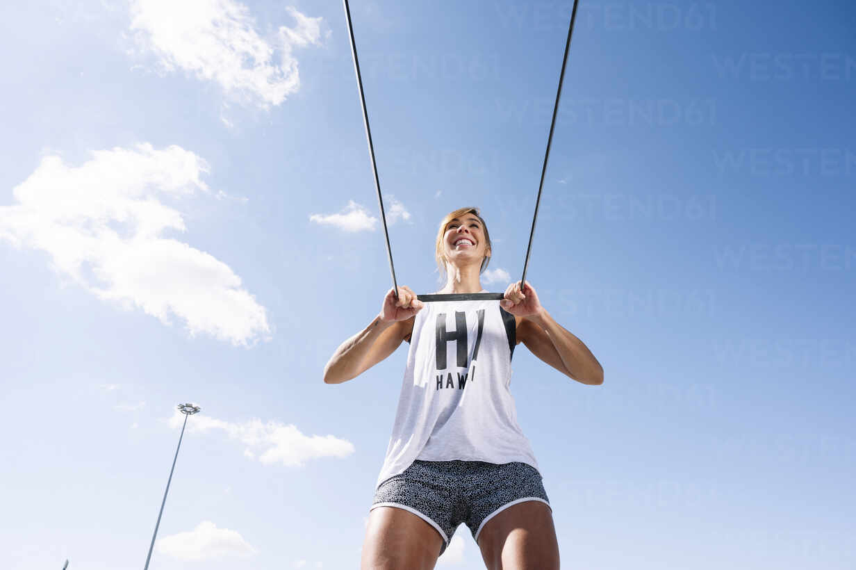Smiling mid adult woman exercising with strap against sky during sunny day - JCMF01133 - Jose Luis CARRASCOSA/Westend61
