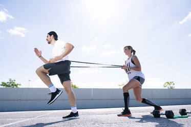 Couple exercising with strap on road against sky during sunny day - JCMF01136