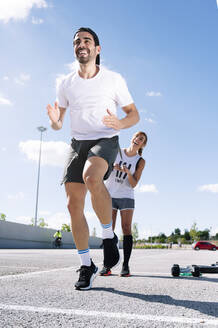 Cheerful couple exercising on street against sky during sunny day - JCMF01139