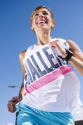 Cheerful woman running against clear blue sky during sunny day - JCMF01148