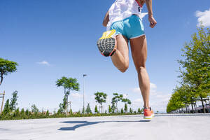 Legs of mid adult woman running on road against blue sky during sunny day - JCMF01151